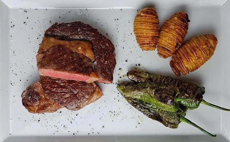 edles-fleisch-rezepte-paul-cooks-lento-ribeye-hasselback-kartoffeln-pimientos-de-padron-angerichtet